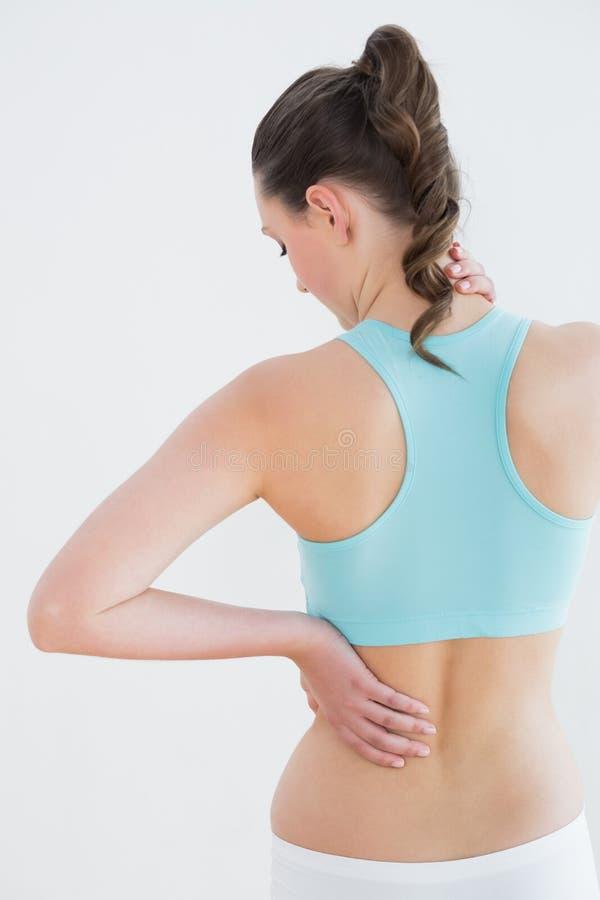 Retrovisione di una donna tonificata con dolore alla schiena contro la parete fotografie stock