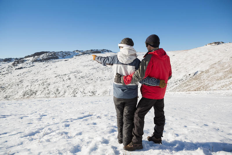 Retrovisione integrale di una coppia che sta sulla neve fotografia stock libera da diritti