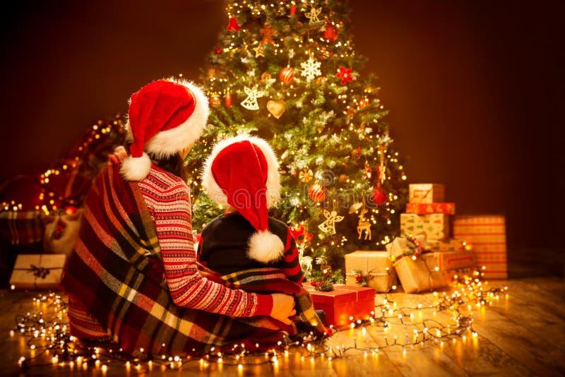 Retrovisione posteriore della famiglia di Natale che guarda all'albero, alla madre ed al bambino di natale in Red Hat fotografia stock libera da diritti