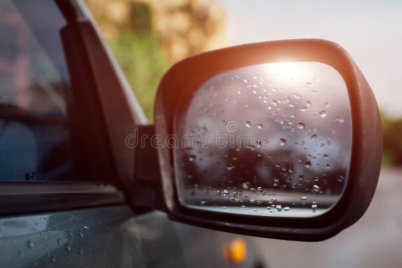 Retrovisor lateral en un coche moderno Descensos lluviosos del agua sobre el vidrio imágenes de archivo libres de regalías