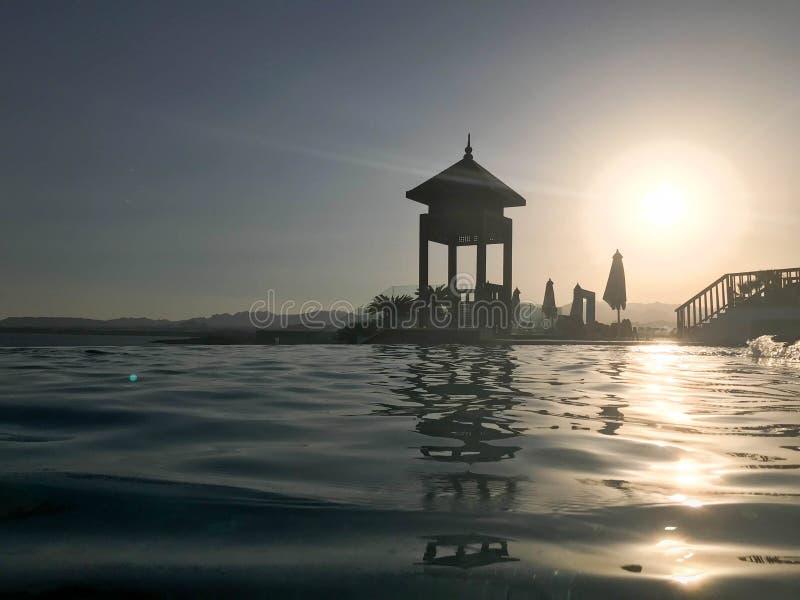 Retten Sie Stand, ragen Sie hoch, retten Sie Beitrag am Rand des Poolunendlichkeitswassers, das mit dem Horizont auf dem Hintergr lizenzfreie stockfotografie