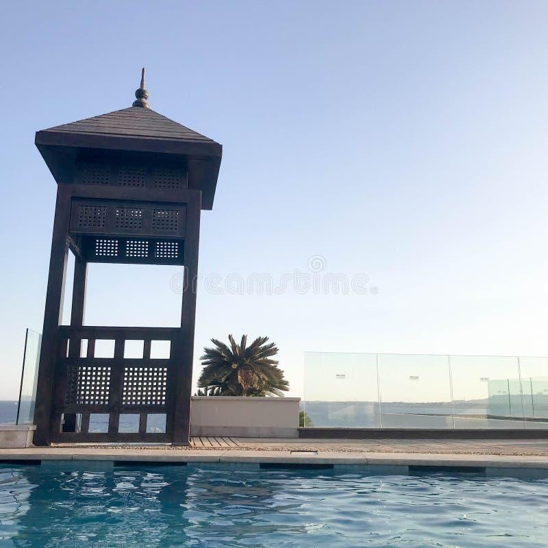Retten Sie Stand, ragen Sie hoch, retten Sie Beitrag am Rand des Wassers eines luxuriösen Unendlichkeitspools, das mit dem Horizo stockfotos