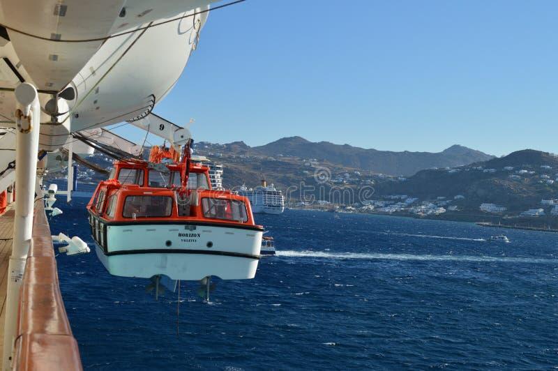Rettungsboot auf einem Kreuzschiff mit Mykonos-Insel in zerstreutem Hintergrund Transport gestaltet Reise-Kreuzfahrten landschaft stockbild