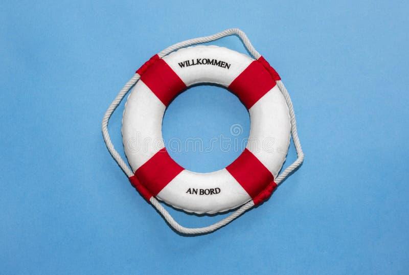 Rettungsgürtel mit Beschriftung 'Willkommen, das ein Bord 'in der deutschen Sprache übersetzt, auf blauem Papierhintergrund 'an B lizenzfreie stockfotografie