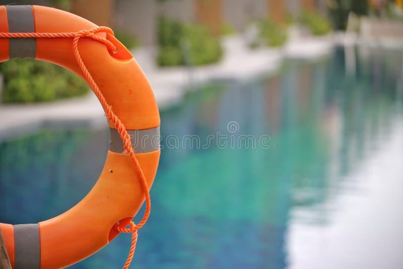 Rettungsring, Schwimmweste, Rettungsring, Rettungsgürtel, der am allgemeinen Swimmingpool im Unschärfehintergrund hängt Zu Konzep stockfotografie