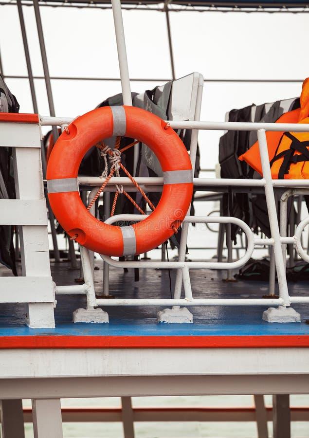 Rettungsring und Schwimmwesten auf einer Fährenplattformnahaufnahme Rettungsausrüstung lizenzfreies stockfoto