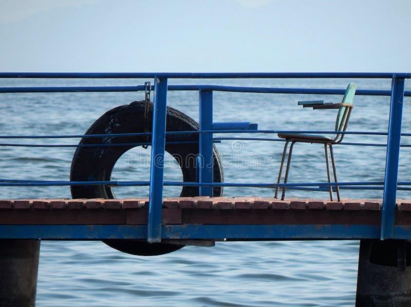 Rettungsring und Stuhl auf dem Flusspier Es ` s alles, das wir, ich benötigen, denkt stockbilder