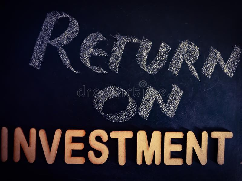 return on investment word displayed on chalkboard concept with wooden alphabet texture royalty free stock photo