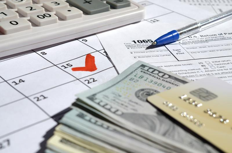 1065 Return of partnership income blank with dollar bills, calculator and pen on calendar page with marked 15th April. Tax period concept. IRS Internal Revenue stock photo