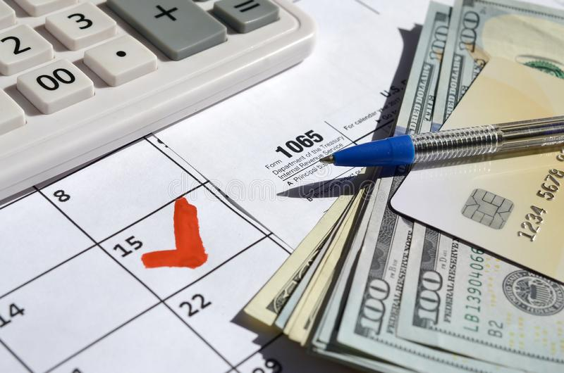 1065 Return of partnership income blank with dollar bills, calculator and pen on calendar page with marked 15th April. Tax period concept. IRS Internal Revenue stock photos