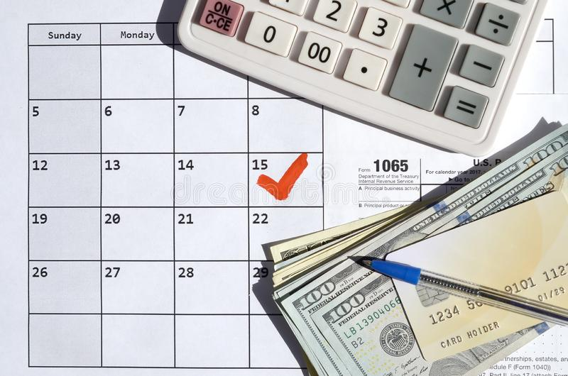 1065 Return of partnership income blank with dollar bills, calculator and pen on calendar page with marked 15th April. Tax period concept. IRS Internal Revenue royalty free stock images