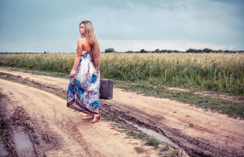 Return of the rural girl to native places. Return of the rural girl with old suitcase to native place royalty free stock images