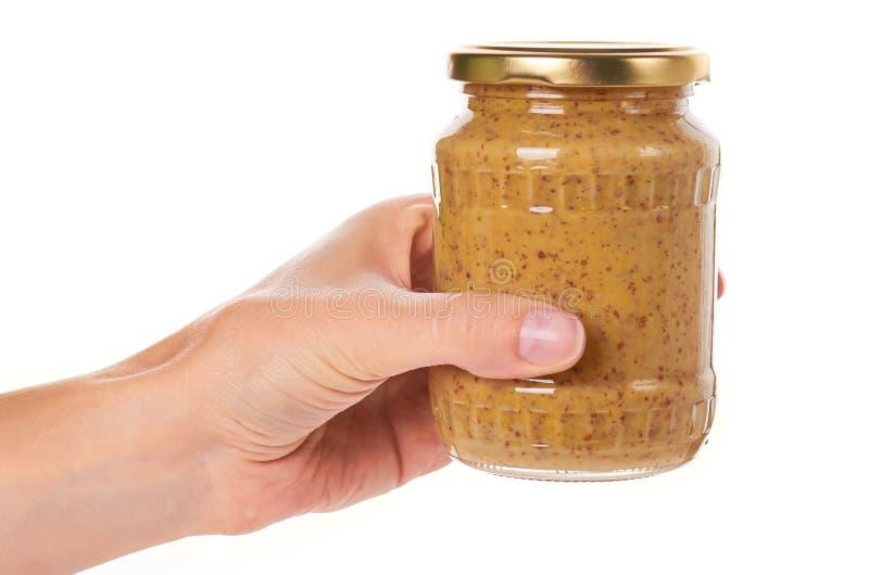 Returnera gjord senap i glasflaska i handen som isoleras på vit bakgrund arkivfoton