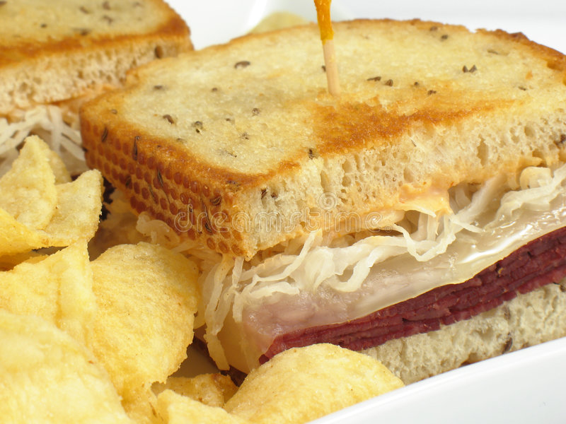 Reuben & Chips. A delicious reuben sandwich: corned beef, melted swiss cheese, sauerkraut, and thousand island dressing on toasted rye bread. Served with potato royalty free stock images