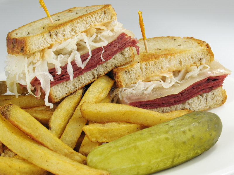Reuben with Fries. A delicious reuben sandwich: corned beef, melted swiss cheese, sauerkraut, and thousand island dressing on toasted rye bread. Served with royalty free stock images