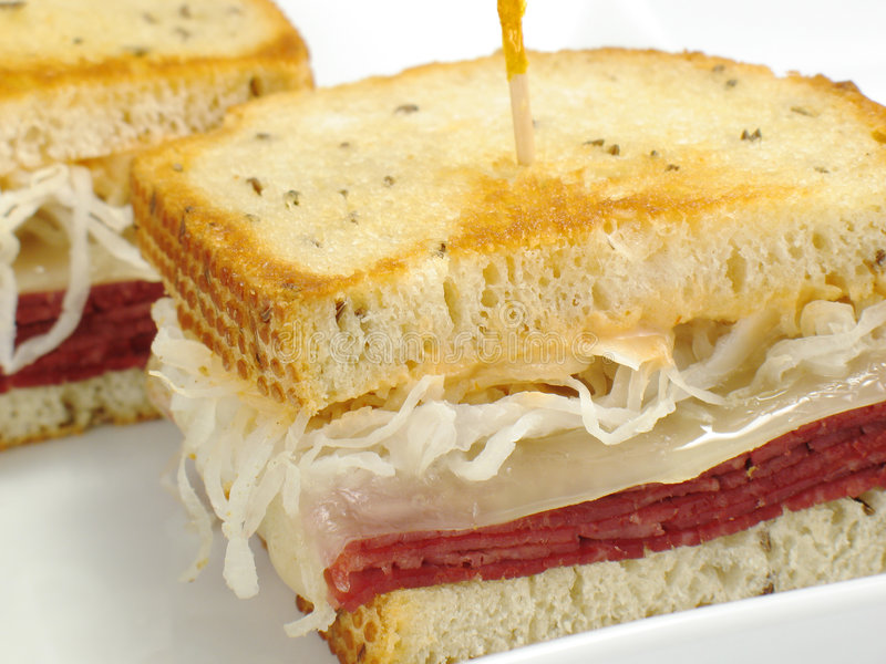 Reuben Sandwich. A delicious reuben sandwich: corned beef, melted swiss cheese, sauerkraut, and thousand island dressing on toasted rye bread stock image