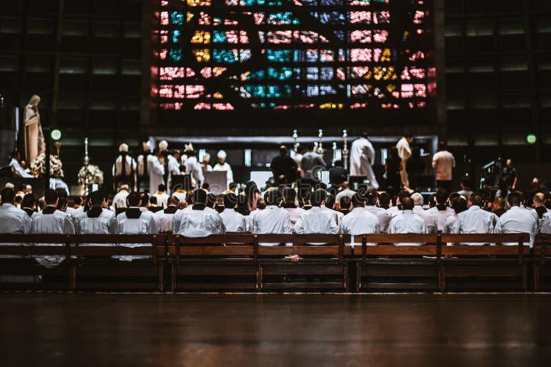 Reuna-se em uma catedral com muitos principiantes nos bancos de madeira imagem de stock royalty free