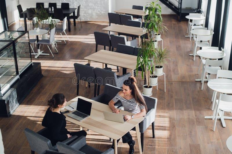 Reunião cara-a-cara Duas mulheres de negócio novas que sentam-se na tabela no café A menina mostra a informação do colega na tela foto de stock royalty free