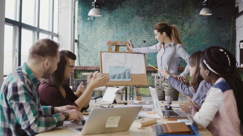 Reunião da equipe do negócio da raça misturada no escritório do sótão Gerente da mulher que apresenta dados financeiros, aplauso  fotos de stock royalty free