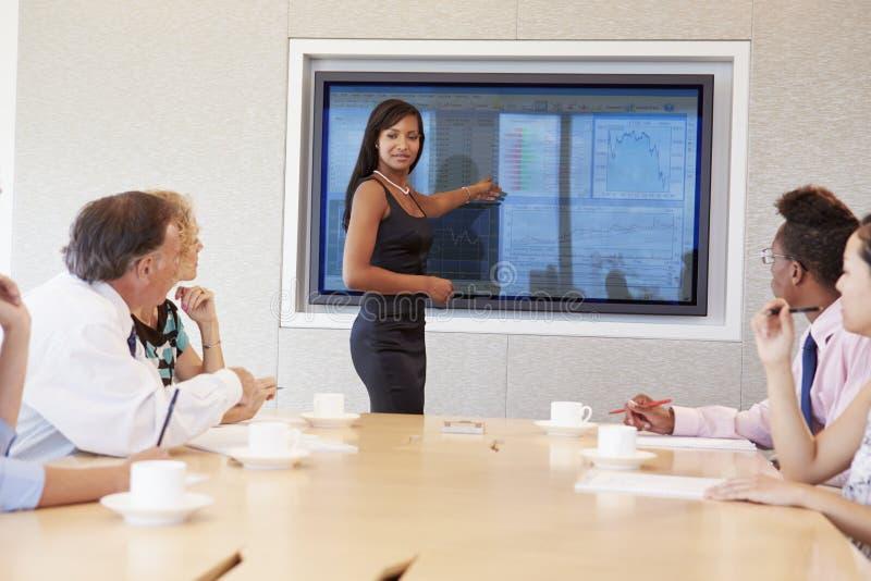 Reunião da sala de reuniões de By Screen Addressing da mulher de negócios fotos de stock royalty free