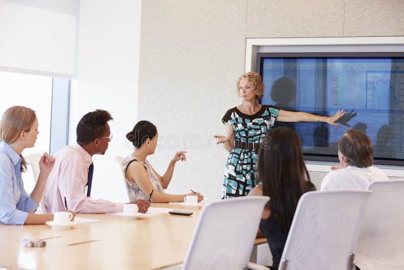 Reunião da sala de reuniões de By Screen Addressing da mulher de negócios fotos de stock