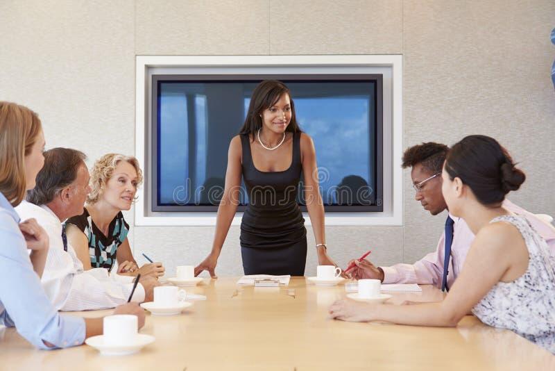 Reunião da sala de reuniões de By Screen Addressing da mulher de negócios fotografia de stock