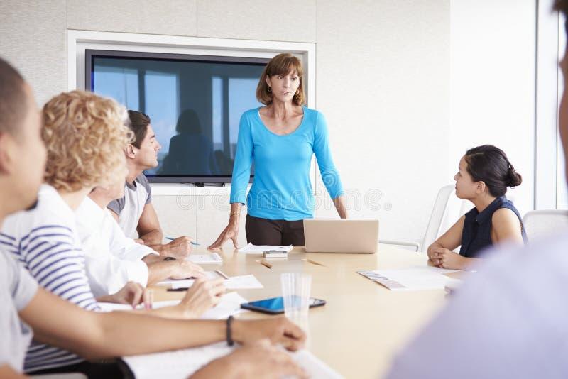 Reunião da sala de reuniões de By Screen Addressing da mulher de negócios foto de stock