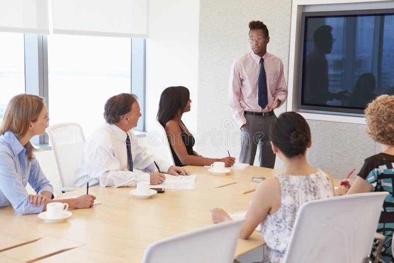 Reunião da sala de reuniões de By Screen Addressing do homem de negócios fotografia de stock royalty free