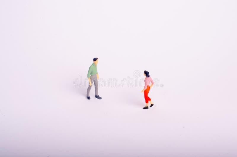 Reunião de dois povos em um fundo branco Um homem e uma mulher vão encontrar-se Relacionamento romântico, reunião do amor, negóci imagem de stock