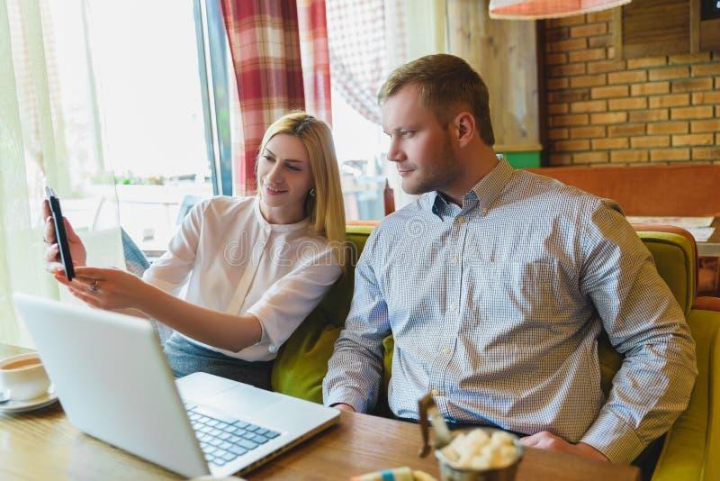 Reunião de negócios em um café Homem e mulher que olham o PC da tabuleta imagens de stock