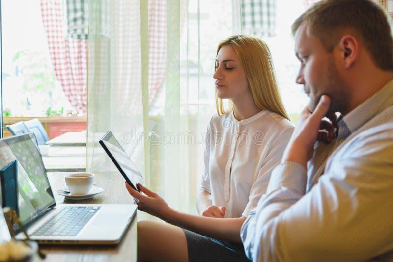 Reunião de negócios em um café Homem e mulher que olham o portátil fotos de stock