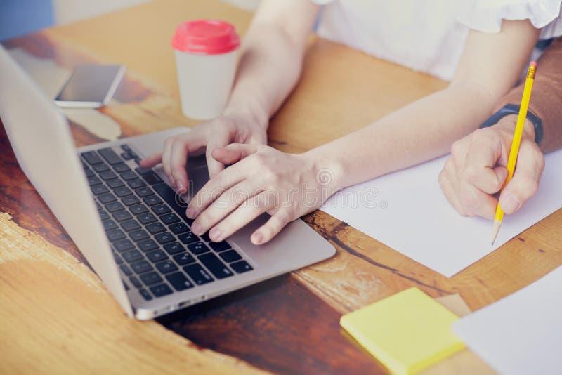 Reunião de negócios no escritório moderno, close-up das mãos da mulher no portátil do teclado na tabela de madeira, escrita da mã fotos de stock royalty free