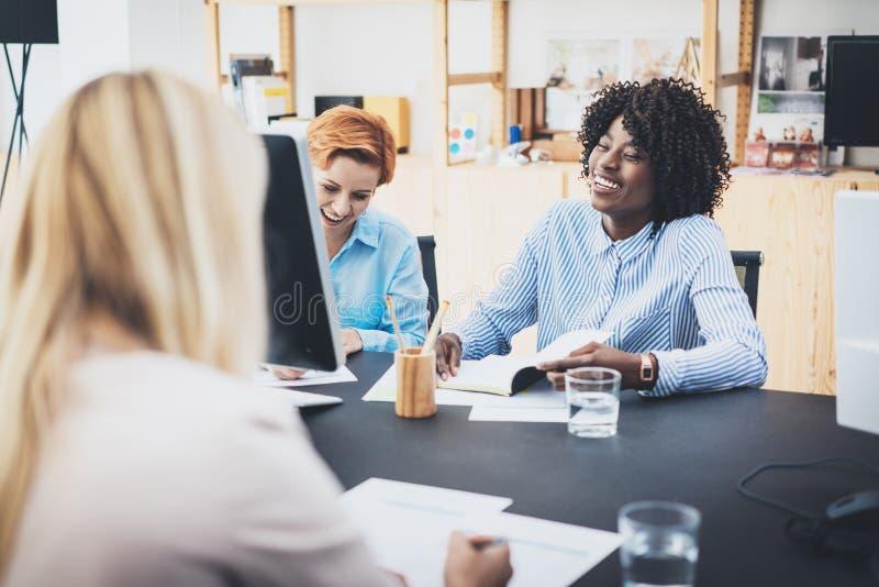 A reunião de negócios rindo da mulher bonita no escritório moderno Colegas de trabalho das meninas do grupo que discutem junto o  foto de stock