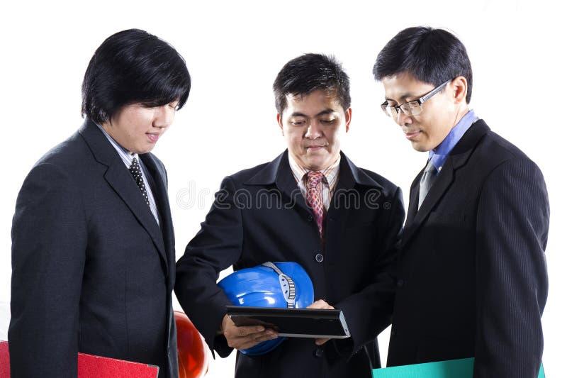 Reunião de três homens de negócios e tabuleta da utilização imagem de stock royalty free