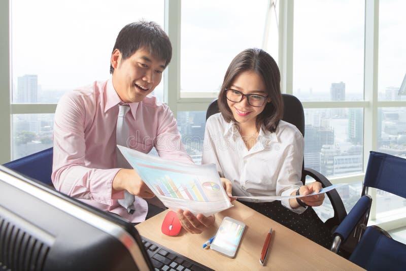 Reunião do homem mais novo e da mulher na cena da tabela de funcionamento do escritório para foto de stock