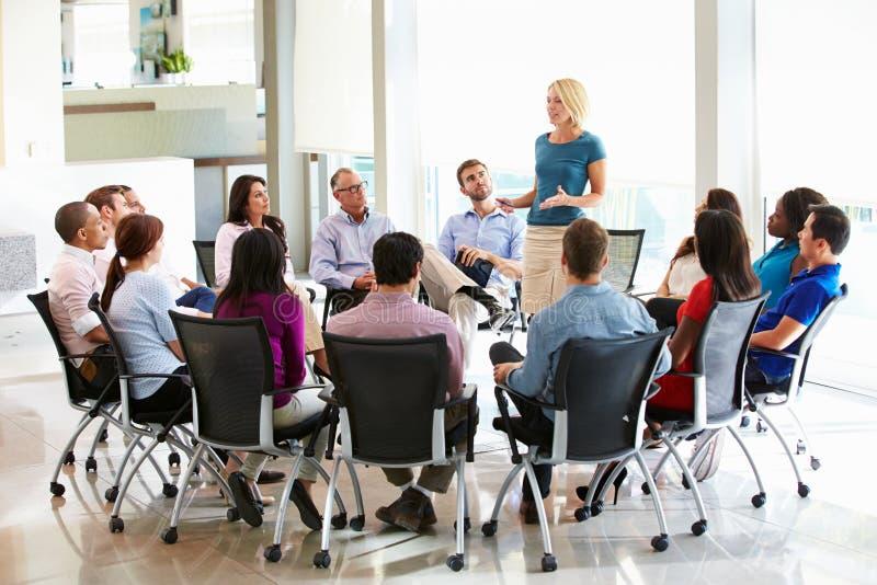 Reunião do pessoal de Addressing Multi-Cultural Office da mulher de negócios imagem de stock royalty free