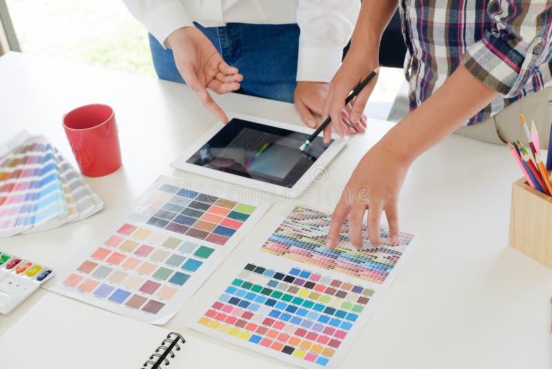 Reunião do projeto gráfico com o tablet pc no local de trabalho imagens de stock