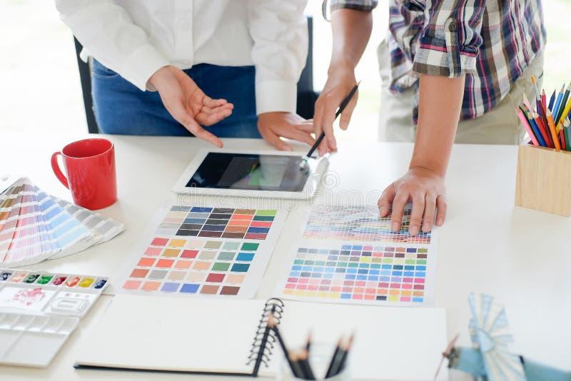 Reunião do projeto gráfico com o tablet pc no local de trabalho imagens de stock royalty free