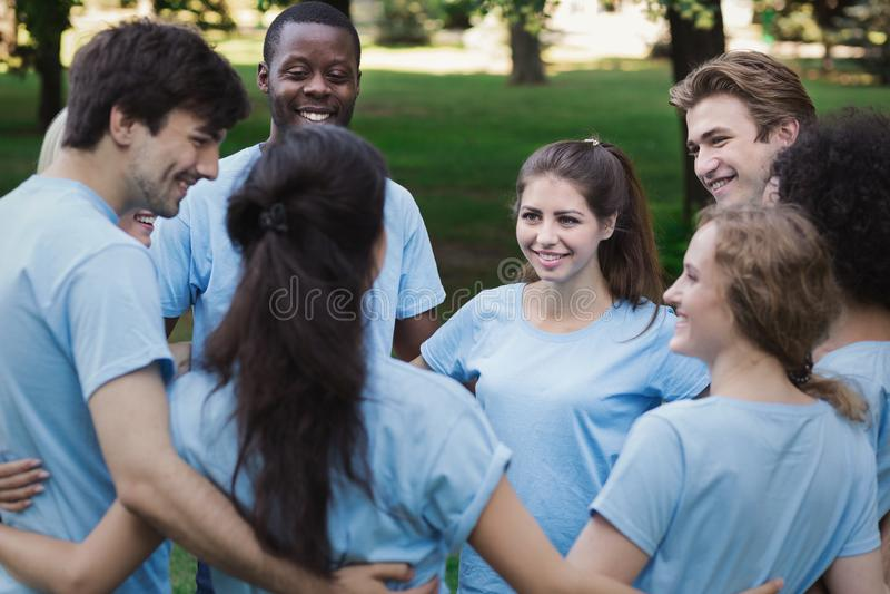 A reunião dos jovens oferece a equipe no parque fotografia de stock royalty free