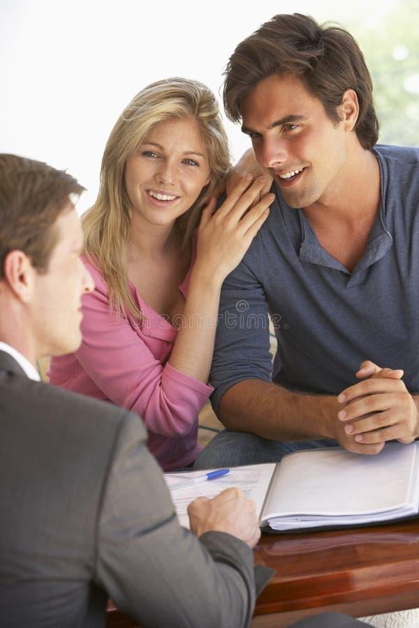 Reunião dos pares com conselheiro financeiro em casa fotografia de stock
