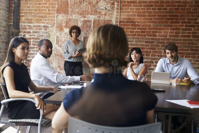 Reunião madura da sala de reuniões de Standing To Address da mulher de negócios fotografia de stock