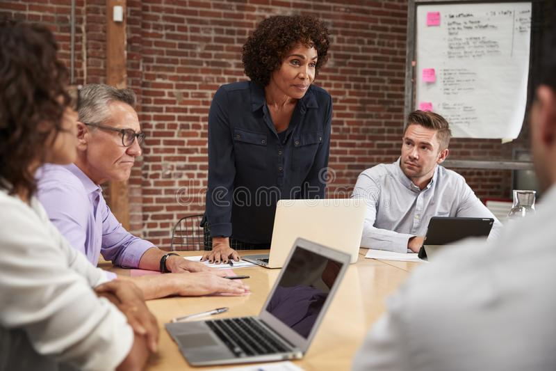 Reunião madura do escritório de Standing And Leading da mulher de negócios em torno da tabela imagem de stock