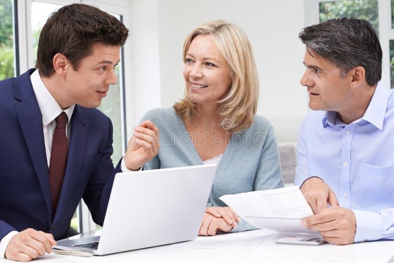 Reunião madura dos pares com conselheiro financeiro em casa foto de stock royalty free