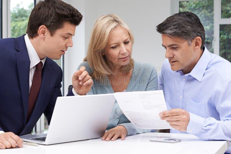 Reunião madura dos pares com conselheiro financeiro em casa fotos de stock