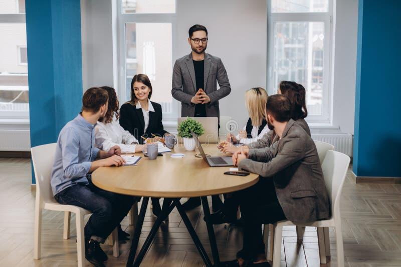 Reunião masculina do diretor empresarial com os trabalhadores de escritório, dando sentidos no escritório moderno à moda imagens de stock royalty free