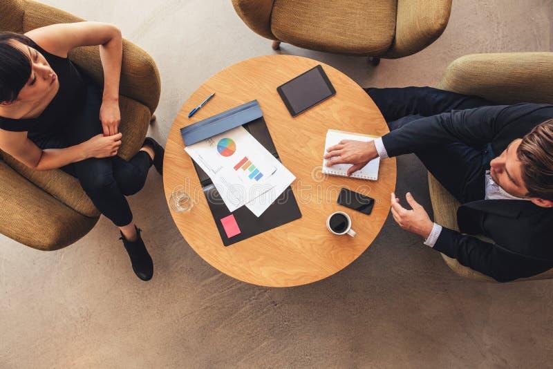A reunião nova do homem de negócios e da mulher no escritório incita fotos de stock royalty free