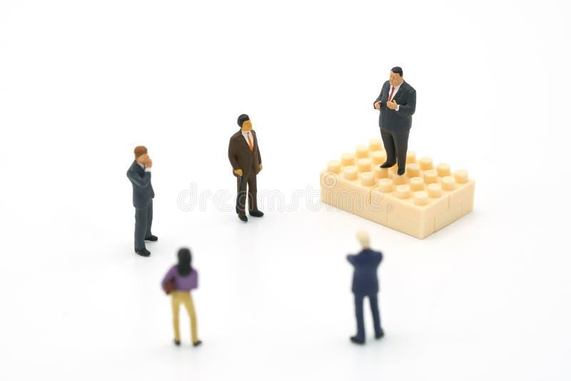 Reunião ou discussão ereta dos povos da miniatura 5 usando-se como o conceito do negócio do fundo com espaços da cópia imagem de stock royalty free