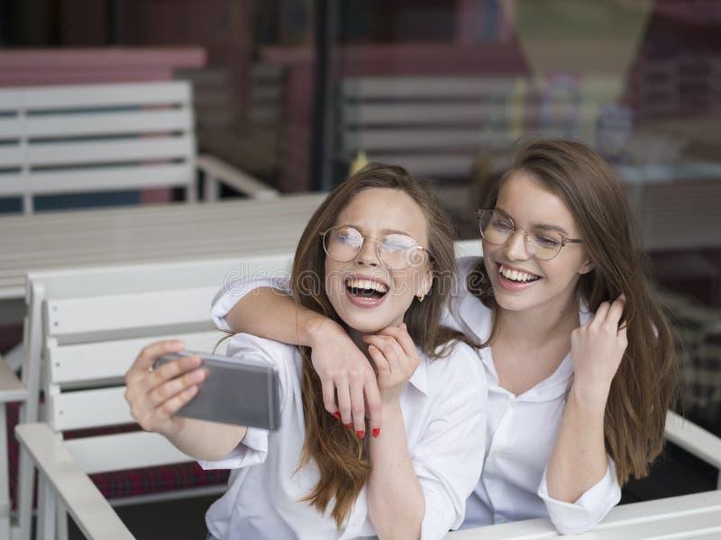 Reunión agradable en un café Holydays del verano Dos muchachas hacen un selfie mientras que se sientan en café del verano fotos de archivo