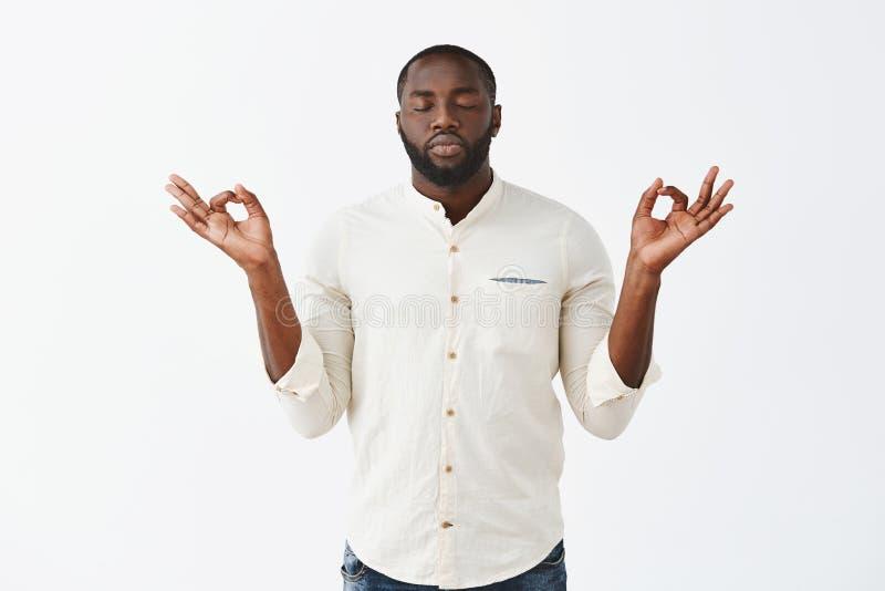 Reunión con anture con la meditación Varón afroamericano apuesto tranquilo en la camisa sport blanca, aumentando las manos imagen de archivo