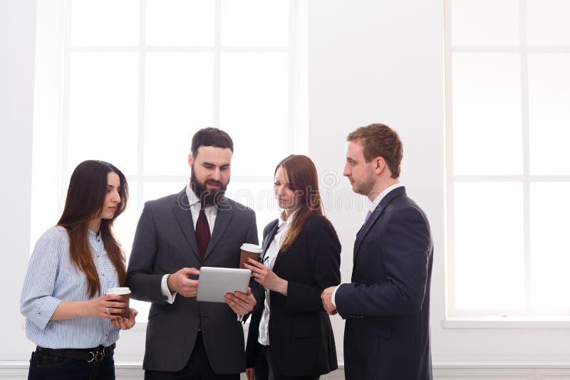 Reunión corporativa de empleados en oficina durante el descanso para tomar café, hombres de negocios con el espacio de la copia fotografía de archivo libre de regalías